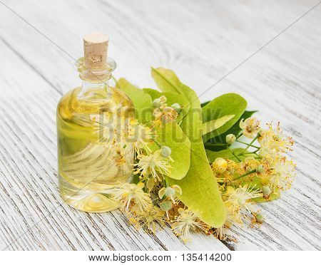 bottle of essential linden oil on a wooden table