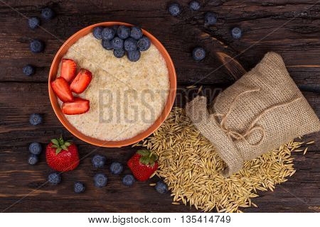 Breakfast with porridge strawberry and blueberry on a wooden table. Top view