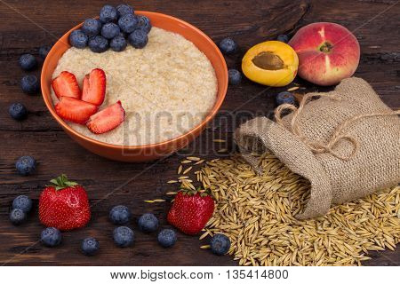 Breakfast with porridge strawberry blueberry and apricots on a wooden table