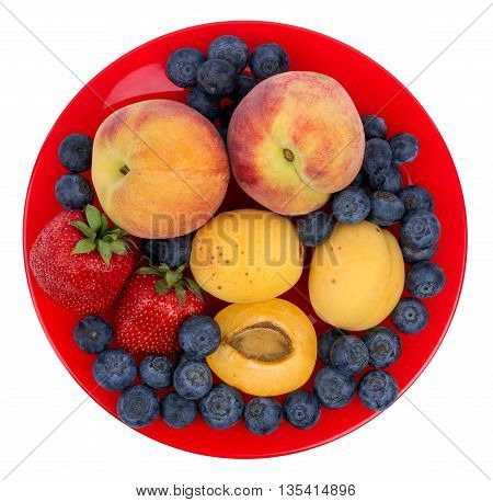 Fresh blueberry strawberry peach and apricot on a red plate isolated on a white background
