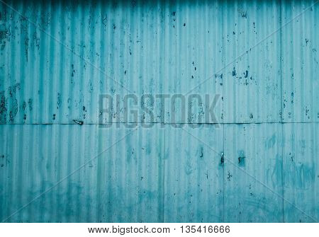 Old Rusty blue wall with the paint peeling off. Damaged Corrugated Surface Background