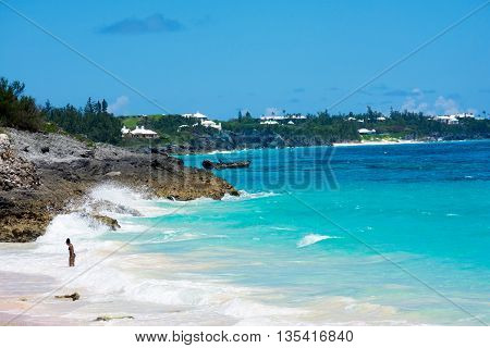Turquoise colored water and white roofed homes off in the distance of this Bermuda seascape.