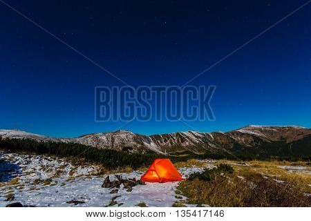 Winter Camping Orange Glowing Tent in Mountain Landscape and Night Sky with Many Stars Red Tent and Snowy Terrain