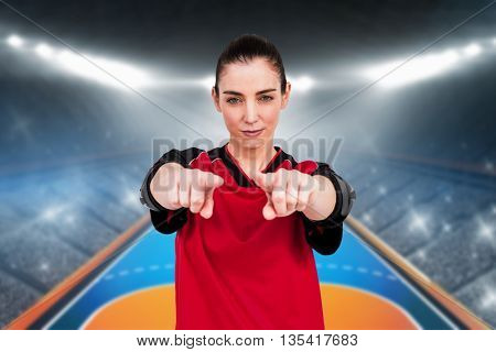 Female athlete posing with elbow pad and pointing the camera against handball field indoor