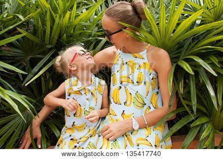 Young mother and her little daughter in tropical garden among green foliage. Both blonde and wearing the same dress.
