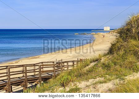 The Regional Natural Park Dune Costiere (Torre Canne): wooden walkway between sea dunes. (Apulia)-ITALY- The park covers the territories of Ostuni and Fasano along eight kilometers of coastline.Beach with sea dunes in the background an angler.