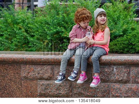 photo of two cute hipsters drinking coctail in park