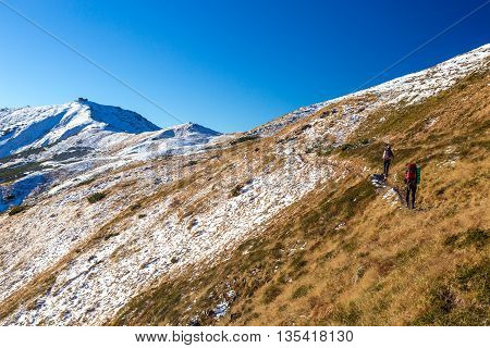 Winter Mountain Range View and Group of Trekkers Walking Up on Trail Carrying Backpacks and Using Hiking Poles Clear Blue Sky