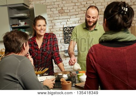 Happy couple and friends talking and cooking together in kitchen.