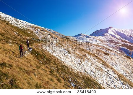 Winter Mountain Range View and Group of Trekkers Walking Up on Trail Carrying Backpacks and Using Hiking Poles Sun Shining on Clear Blue Sky