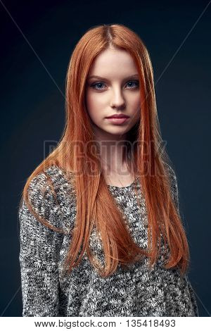 Portrait of beautiful red haired female in grey sweater