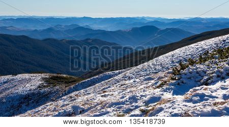 Snowbound Mountain Slope and Foggy Distant Ridges in Winter with many layers prospective and foggy remote ridges