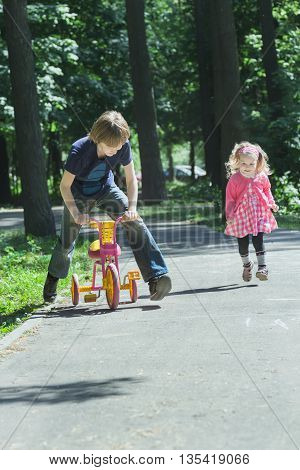 Sibling children are playing tag game by running and riding kids tricycle