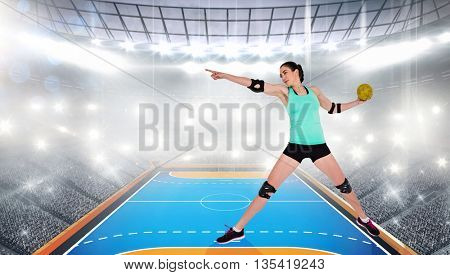 Female athlete with elbow pad throwing handball against handball field indoor