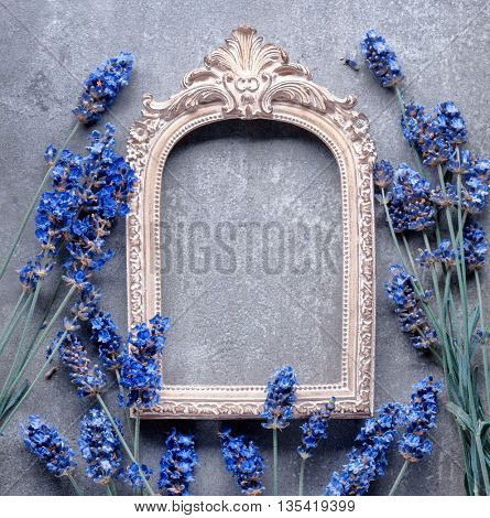 Vintage picture frame with lavender flower on stone background