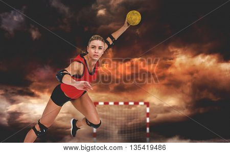 Female athlete throwing handball against aerial view of a city on a cloudy day