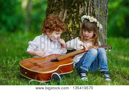 photo of cute little children playing guitar
