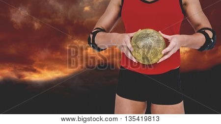 Female athlete with elbow pad holding handball against gloomy sky