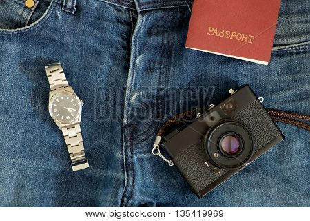 Collection of traveler clothes and objects on jeans