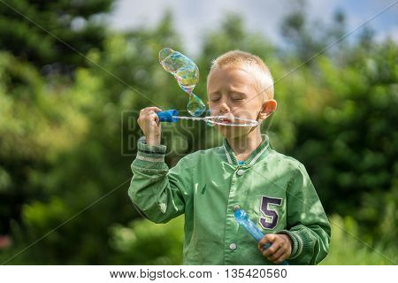 Little boy playing in the garden and have fun with blowing soap bubbles