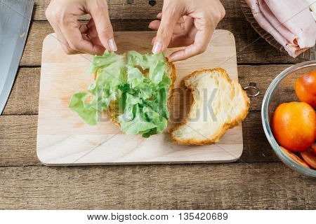 Food series : Making croissant sandwich, woman's hands placing lettuce on croissant sandwich