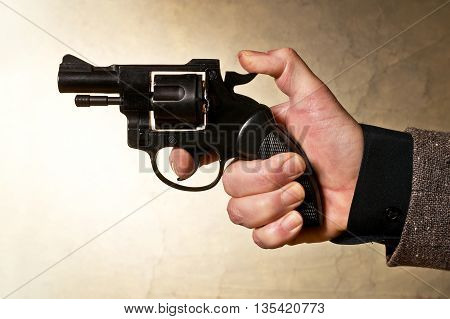 Silhouette of a mans hand with a handgun in brown