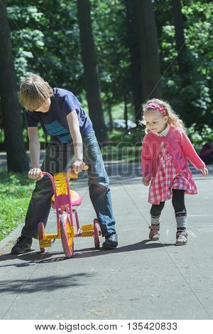 Siblings are playing with pink and yellow kids tricycle on park tarmac footpath