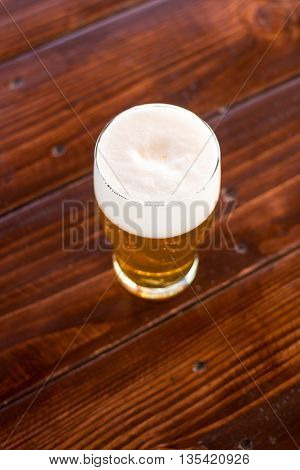 Full glass of beer foam is on the table