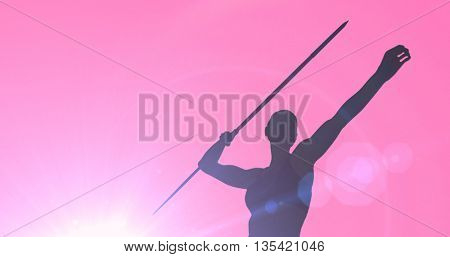 Low angle view of sportswoman is practising javelin throw against pink background