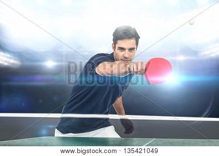 Portrait of male athlete playing table tennis against american football arena