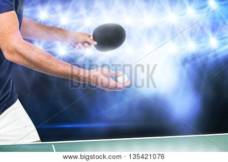 Male athlete playing table tennis against view of lights