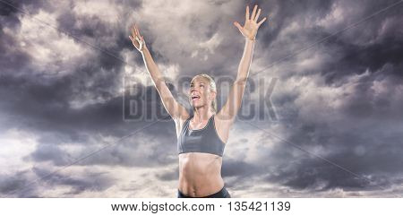 Female athlete posing after victory against gloomy sky