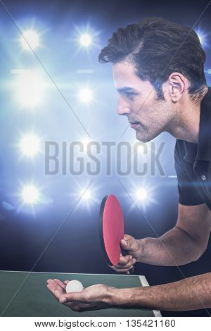 Confident male athlete playing table tennis against composite image of blue spotlight
