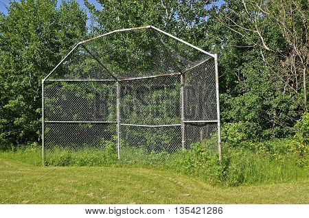 An old baseball backstop sets by itself along a tree line