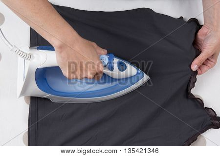 High Angle View Of Woman Ironing On Ironing Board