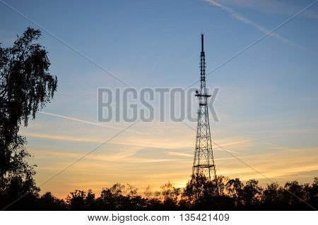 Steel radio tower with trees on the left and bottom at sunset coloring the sky blue and orange