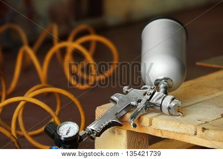 Spray gun on wooden stand, closeup