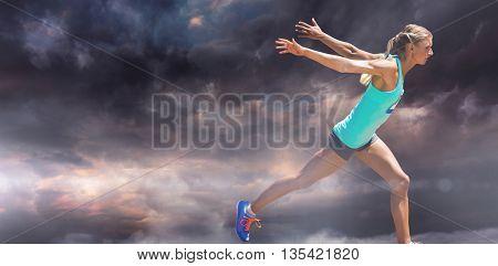 Sportswoman finishing her run against gloomy sky