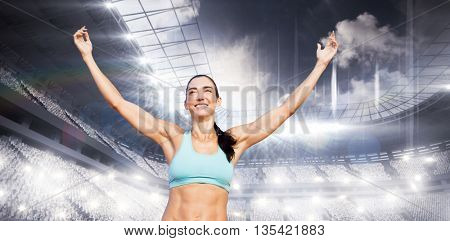 Portrait of happy sportswoman is raising arms against sports arena