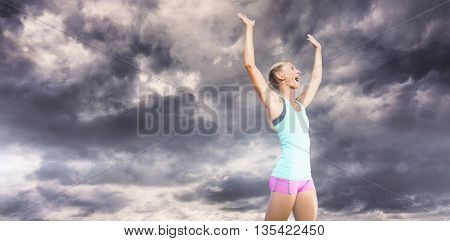 Sporty woman celebrating her victory against gloomy sky