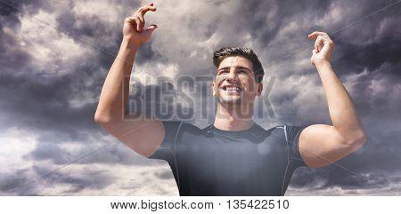 Portrait of happy sportsman against gloomy sky