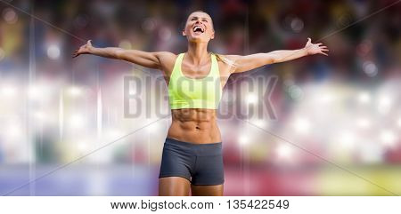 Fit woman celebrating victory with arms stretched against sports arena