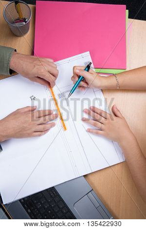 Architects Working On Plans At A Business Boardroom Table
