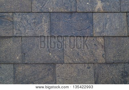 Dark gray paving slabs close up for background
