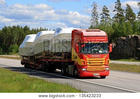 PAIMIO, FINLAND - JUNE 12, 2016: Scania R420 semi transports boats as oversize load along motorway in South of Finland.