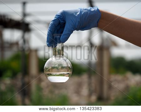 Hand in glove holding a retort with clear water. Background sky. or power plant construction