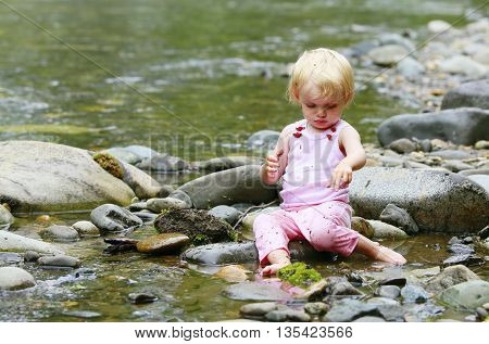Dirty Little Girl In A Pink Suit Sitting On The Rocks In The River