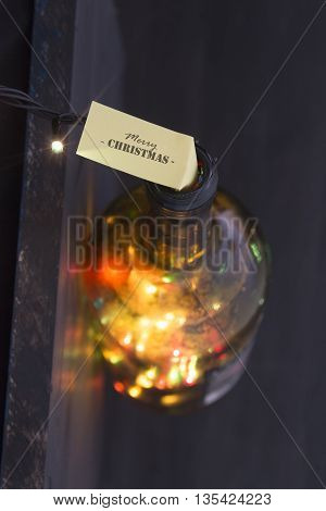 Merry Christmas idea, label and bottle with colored lights