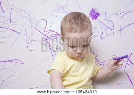 Baby boy drawing with wax crayon on plasterboard wall