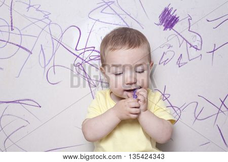 Baby boy drawing with wax crayon on plasterboard wall. He has the crayon on the mouth thinking what to do